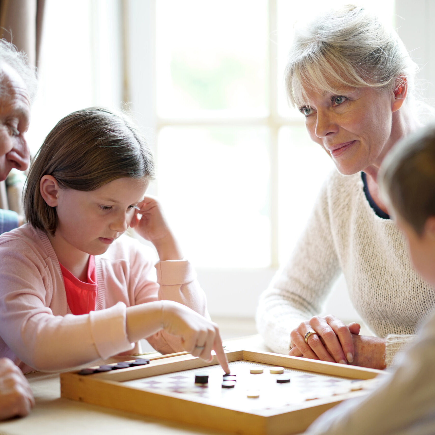 Grand-parents with grandkids playing checkers