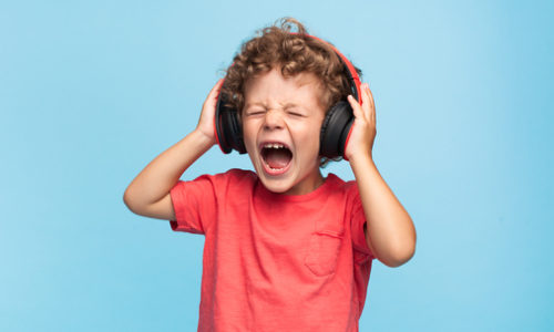 Curly boy in headphones screaming with eyes closed on blue background.